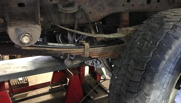 Photo showing extra leaf springs being added to a heavy duty truck at Dias Spring Service in Erie, PA.