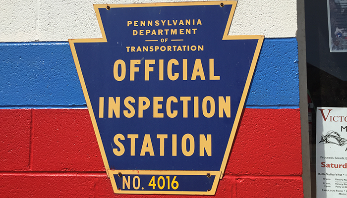 Official PA Inspection Station sign on the building at Dias Auto Service 364 West 12th Street in Erie, PA.